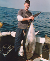 Man holding bluefin tuna by the tail, head down, on charter fishing boat