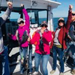 Five people, each holding up sea bass, smiling, on board fishing vessel Magic