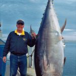 Giant bluefin tuna with smiling man after Magic Charters fishing trip