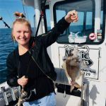 Girl holding up fish caught on Magic Charters fishing trip