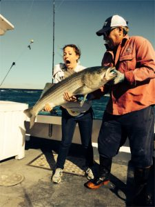 Woman with mouth open in surprise holding striped bass