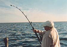 Man fishing with rod bent over, fish on it