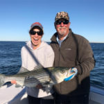 Woman smiling with mouth open holding a very large striped bass, captain beside her