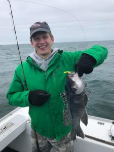 Teenage boy holding up sea bass that he caught on fishing trip