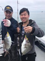 Two young men holding up porgies caught on charter fishing trip