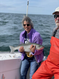 Smiling woman holding huge striped bass